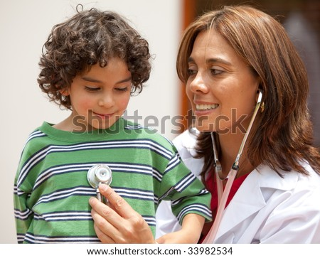 female pediatrician and a little boy where both are smiling - stock photo