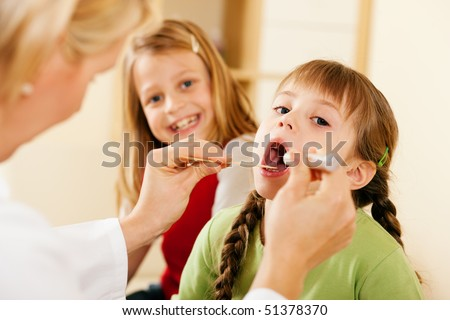 Female pediatrician doctor examining throat of a girl, in the background her sister is waiting to be examined as well - stock photo