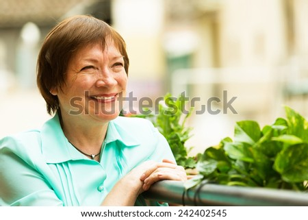 Female pensioner resting at balcony with flowers and smiling - stock photo