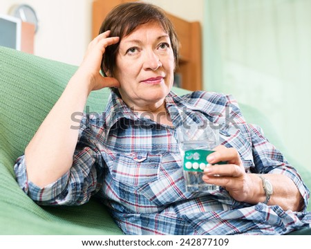 female pensioner with pills and glass of water indoor - stock photo