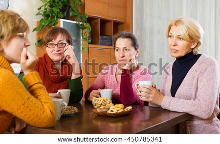 Female pensioners listening to sad story of their friend at table - stock photo