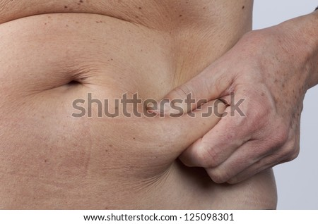 female person checking her belly fat - stock photo