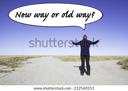Female person standing at a parting of the ways in the desert. Not knowing where to go she is lifting her arms. In a speech balloon is written the question: New way or old way?     - stock photo