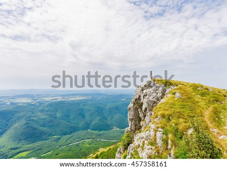 Female person stands on top of mountain enjoys view in summertime