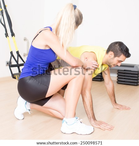 female personal trainer helps with functional training exercise - stock photo