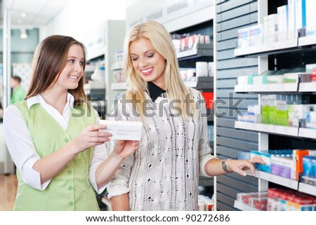 Female pharmacist advising customer at pharmacy - stock photo