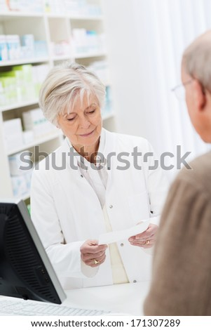 Female pharmacist checking a prescription behind the counter watched by a patient