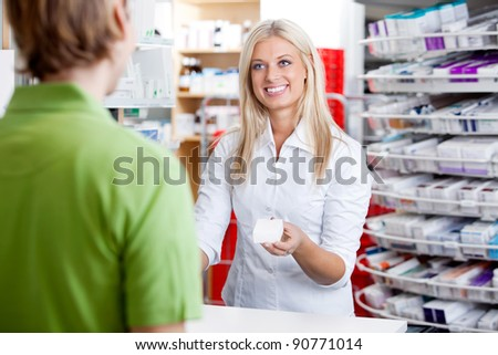 Female pharmacist giving medicine to customer at counter - stock photo