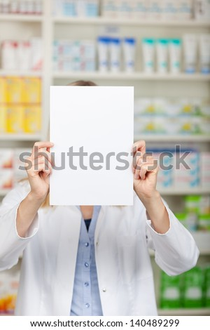Female pharmacist holding blank paper in front of face in pharmacy - stock photo