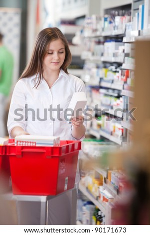 Female pharmacist in drugstore stocking shelves - stock photo