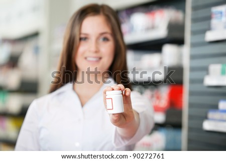 Female pharmacist looking at camera recommending medicine - stock photo