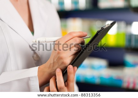 Female pharmacist or assistant is doing inventory or order taking in pharmacy - stock photo