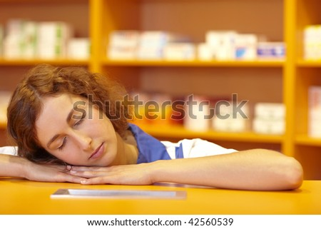 Female pharmacist sleeping with head on counter