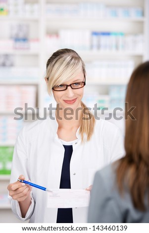 Female pharmacist talks to patient about the medical prescription inside the pharmacy