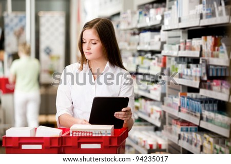 Female pharmacist working in pharmacy with digital tablet and medicine - stock photo