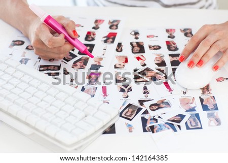 Female photo editor working on a contact sheet with a pink marker - stock photo