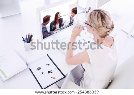 Female photo editor working on computer against attractive businesswoman laughing with her team - stock photo
