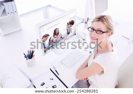 Female photo editor working on computer against glad businesswoman talking to her team - stock photo