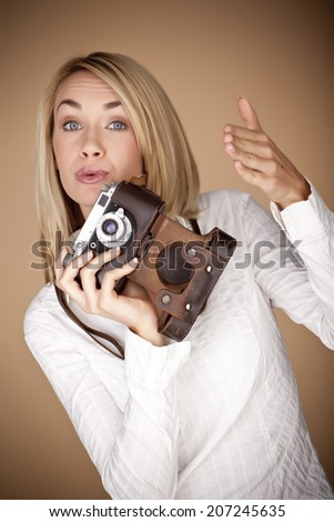 Female photographer holding a vintage camera over a brown background. - stock photo