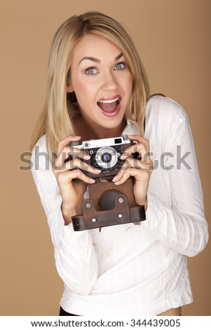 Female photographer holding a vintage camera over a brown background.