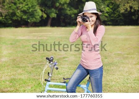 female photographer holding camera and sitting bike - stock photo