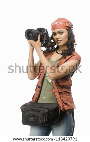 Female photographer photographing with digital camera - stock photo