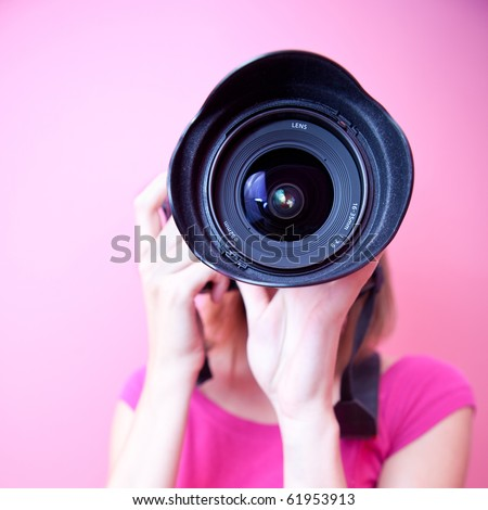 female photographer pointing her super wide lens at you (color toned image) - stock photo