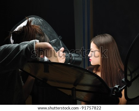 Female photographer shooting close up model's lips in studio - stock photo
