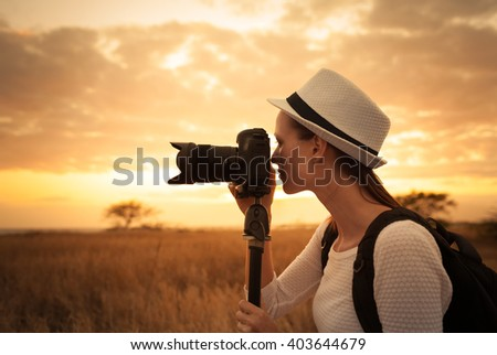Female photographer shooting in a beautiful outdoor setting. - stock photo