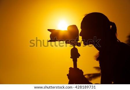Female photographer shooting outdoors.  - stock photo