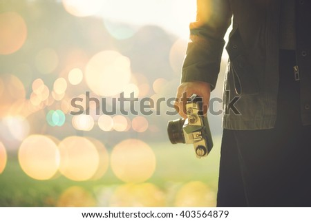 Female photographer shooting outdoors on autumn afternoon sunlight, retro toned image with selective focus on hand holding generic vintage photo equipment. - stock photo