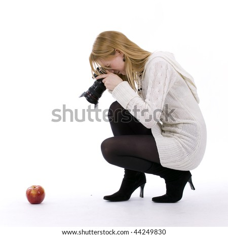 Female photographer shooting red apple by professional digital camera - stock photo
