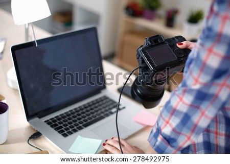 Female photographer sitting on the desk with laptop - stock photo