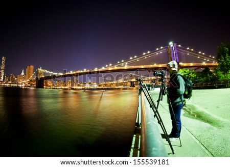 Female photographer taking a picture in front of Brooklyn Bridge - stock photo
