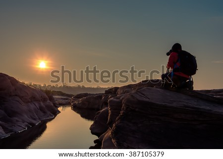 Female photographer taking photo on the rock with sunrise landscape - stock photo