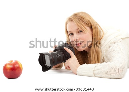 female photographer with professional digital camera and apple - stock photo