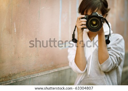 female photographer with professional SLR camera, natural light, selective focus on nearest part of lens with blend - stock photo