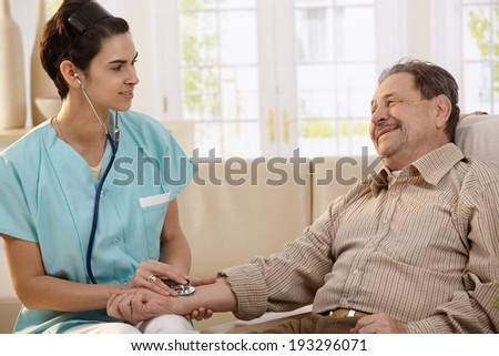 Female physician using stethoscope and measuring blood pressure of senior man at home.