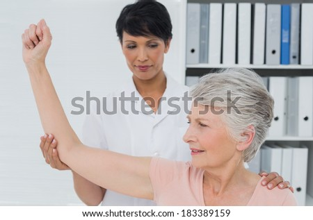 Female physiotherapist assisting senior woman to stretch her hand in the medical office - stock photo
