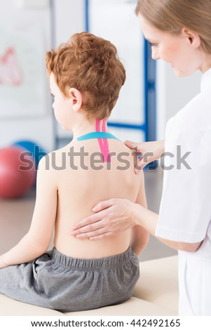Female physiotherapist conducts an examination on young boy