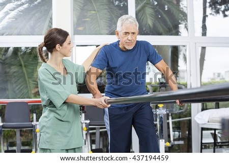 Female Physiotherapist Motivating Senior Patient To Walk Between - stock photo