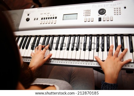 Female piano player, view from the top, body and buttons of the piano were digitally modified - stock photo