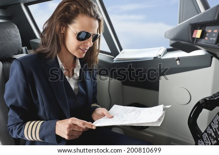 Female pilot with map in airplane cockpit - stock photo