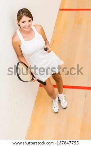 Female player of squash holding racket and ball - stock photo