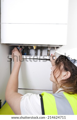 Female plumber servicing central heating boiler - stock photo