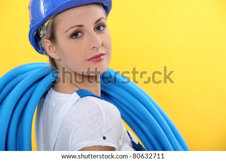 Female plumber with blue pipe