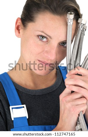 Female plumber with handful of pipes