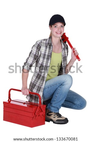 Female plumber with wrench and tool kit - stock photo