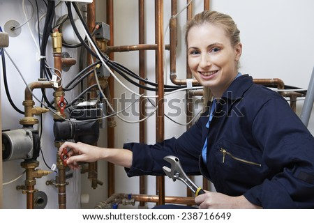 Female Plumber Working On Central Heating Boiler - stock photo