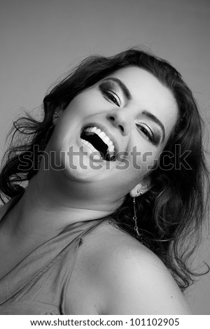 Female Plus size model posing in the studio, bw face portrait, on grey background. The woman is smiling in a happy manner. Good for concept of health, happiness, dieting, obesity, weight loss. - stock photo
